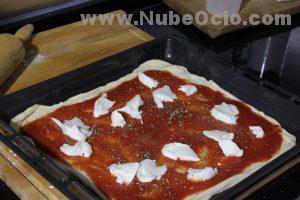 Echando mozzarella a la pizza