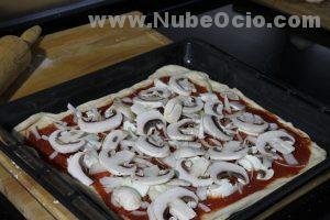 Echando champiñones a la pizza