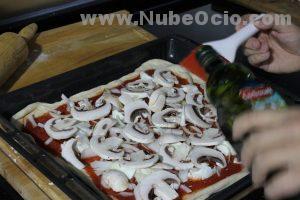 Añadiendo aceite de oliva a la pizza con un pincel