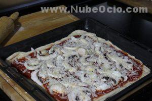 Echando parmesano a la pizza