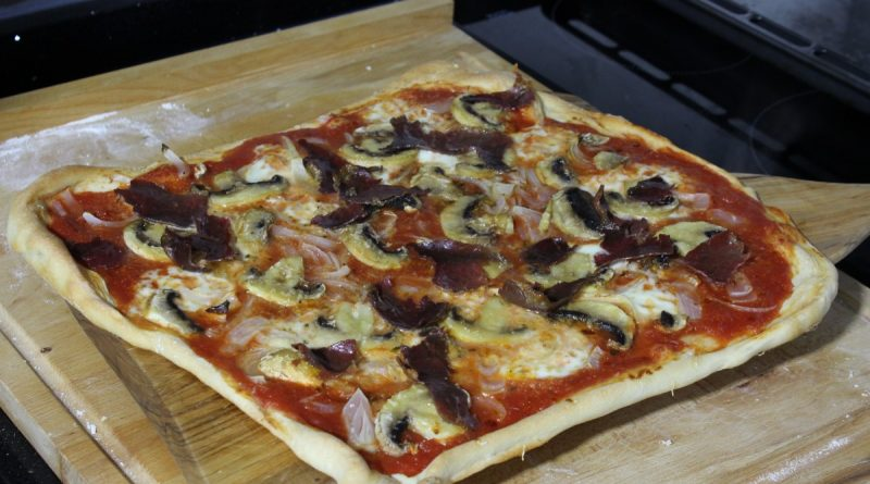 Pizza cocida, con tomate, ajo, orégano, mozzarella, cebolla, champiñones, aceite de oliva y cecina